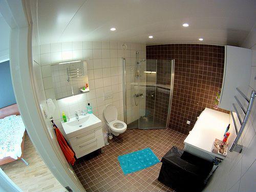 Banheiro com piso marrom e tapete turquesa da MaWá e do Weno.