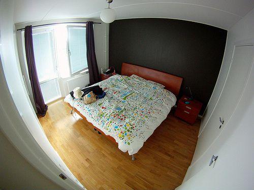 Quarto de casal com parede escura e cama vermelha da MaWá e do Weno.