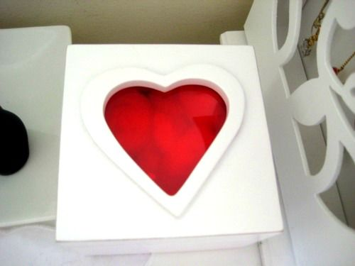 Caixa branca com tampa de acrílico vermelha em forma de coração.