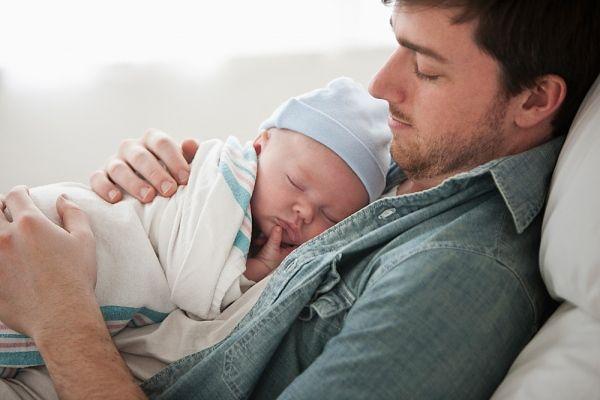 Pai com bebê recém-nascido no colo. Foto: Inmagine.