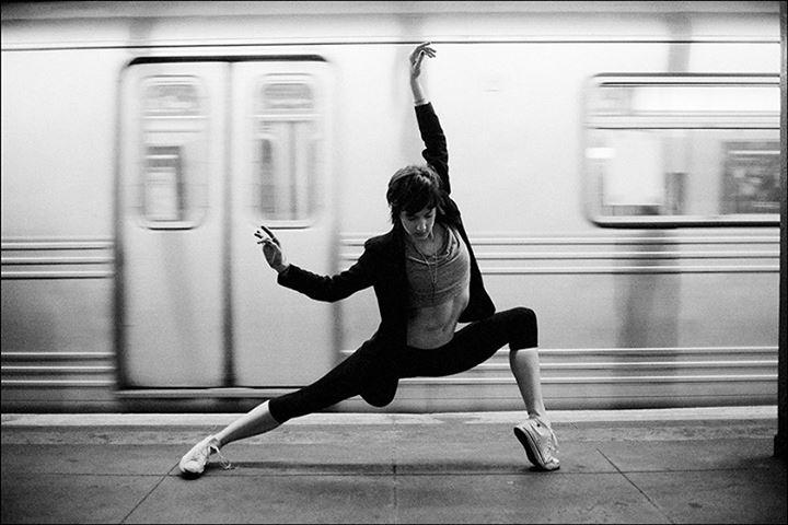 Ballerina Project: bailarina fazendo passo de dança moderna em frente ao metrô.